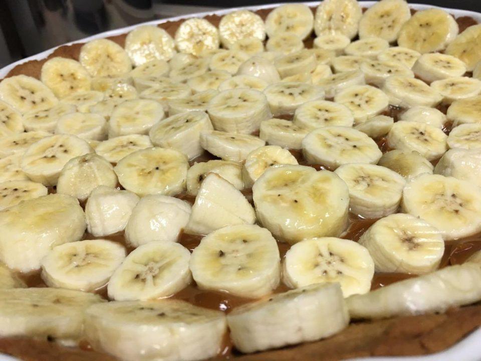 Massa já assada e fria, doce de leite, bananas em rodelinhas.